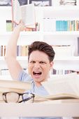 Angry Student With Expression Surrounded By Books  Throwing A Book