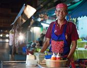 BANGKOK, THAILAND - JANUARY 9, 2012: Local man stands behind his street food stall and smiles to the
