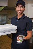 Happy pizza delivery man showing credit card machine in a commercial kitchen