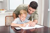 Happy father helping son with math homework at table at home in kitchen