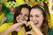 Cheerful couple of Australian or Brazilian or Cameroonian girlfriends soccer fans.