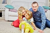 Family of three sits on carpet in light room, daughter ahead, parents behind, mother whispers someth