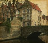 A piece of old architecture in  Bruges, Belgium. Photo in retro style. Added paper texture.