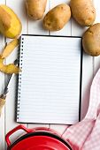 recipe book with potatoes on kitchen table