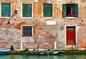 Old brick house with wooden shutters on small canal in Venice, Italy.