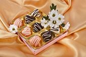 chocolate marchpane hearts candies  with  chrysanthemum daisy on golden silk textured cloth background