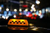 image of cabs  - lluminated traditional yellow taxi sign on top of a cab in a city street with a colourful bokeh of urban lights - JPG