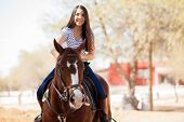 pic of saddle-horse  - Young Latin woman enjoying a horse ride on a sunny day - JPG