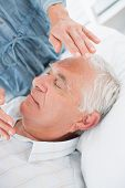 Closeup of senior man receiving Reiki treatment by therapist at health spa