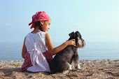pic of schnauzer  - beautiful little girls embracing her dog looking at the sea  - JPG