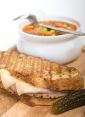 Delicious panini made with ham, pork and swiss cheese served with a vegetable soup, and pickles