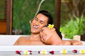 Indonesian Asian couple in wellness beauty day spa having aroma therapy bath with essential oils or
