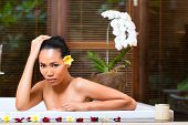 Indonesian Asian woman in wellness beauty day spa having aroma therapy bath with essential oils or s