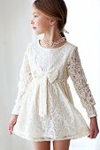 Fashion 7 years old model dressed in ivory lace dress pastel tone