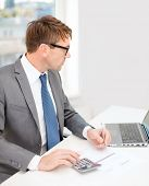 business, office, school and education concept - businessman with laptop computer, papers and calcul