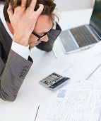 tax, business and stress concept - stressed businessman with papres, laptop and calculator