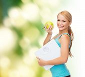 diet, sport and healthcare concept - beautiful sporty woman with scale and green apple