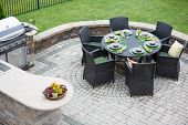 picture of catering  - Elegant outdoor living space on a paved brick patio with a summer kitchen and barbecue and a table laid with formal place settings for dinner high angle view - JPG