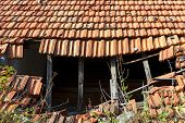 picture of rafters  - Detail of a damaged and abandoned roof with broken tiles and beams - JPG