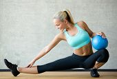 fitness, sport, training and lifestyle concept - smiling woman with exercise ball in gym