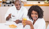 Happy couple having breakfast together at table at home in the kitchen