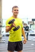 sport, fitness, lifestyle and people concept - smiling man with dumbbell in gym