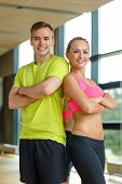 sport, fitness, lifestyle and people concept - smiling man and woman in gym