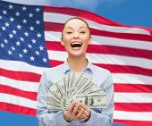 business, holidays and people concept - laughing businesswoman with dollar cash money over american