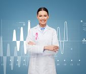 healthcare and medicine concept - smiling female doctor with pink cancer awareness ribbon over graph
