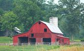 pic of outhouses  - Large Red Barn with a silo and outhouse in the background - JPG