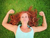 a pretty woman lying in green grass