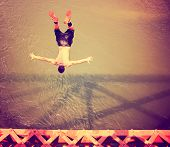 a boy jumping of an old train trestle bridge into a river toned with a retro vintage instagram filte