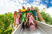 stock photo of chute  - View from below of many kids on playground chute being happy together - JPG