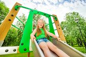 stock photo of chute  - Laughing girl on children chute ready to slide and holding the sides of metallic chute - JPG