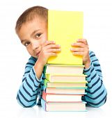 Cute little child plays with book while sitting at table, isolated over white