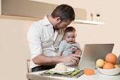 Multi-tasking father with baby while working at home
