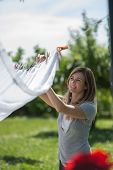image of homemaker  - Young woman hanging up laundry - JPG