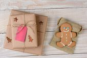 High angle shot of two Christmas presents and a gingerbread man on a whitewashed wood table. The coo