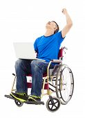 Young Man Sitting On A Wheelchair And Raising Arm