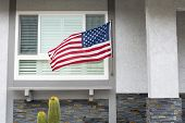 American flag blowing in the breeze while hanging on a residential home symbolizes a patriotic holid