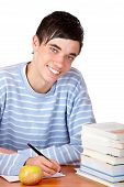 Young Happy Handsome Male Student Sitting On Desk Learning With Study Books