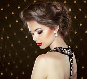 Fashion Brunette Model Portrait. Jewelry And Hairstyle. Elegant Lady Over Bokeh Lights Background