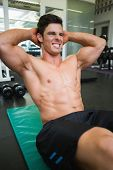 Determined young muscular man doing abdominal crunches in gym