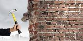 Close up of businessman hand crashing brick wall