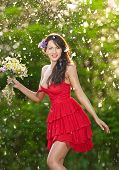 Young voluptuous brunette holding a wild flowers bouquet in a sunny day. Portrait of beautiful woman