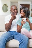 Happy couple relaxing on the couch having coffee at home in the living room
