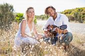 image of serenade  - Handsome man serenading his girlfriend with guitar on a sunny day - JPG