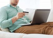 technology, shopping, banking, home and lifestyle concept - close up of man with laptop computer and