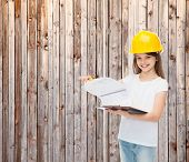 childhood, construction, architecture, building and people concept - smiling little girl in protective helmet with clipboard turning page