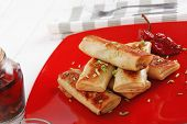 russian food - meat wrapped in a pancake with red hot pepper  and pickled mushrooms served on red pl